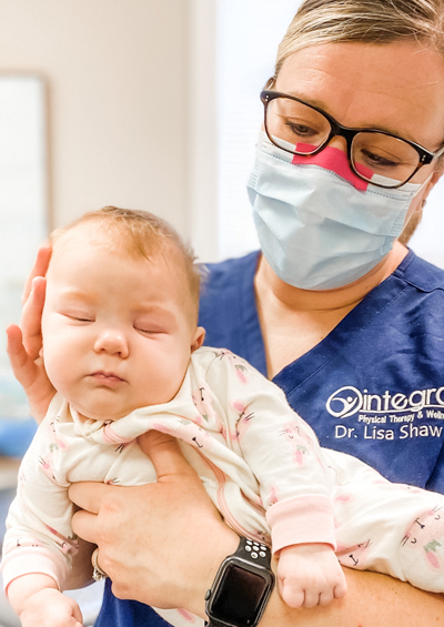 Dr. Lisa Shaw providing physical therapy services to an infant